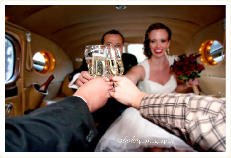 Bride and groom celebrating their wedding toast in the interior of their rental 1939 Packard