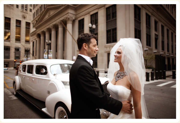 Wedding couple downtown Chicago with their luxury Classic Wedding Car 1939 white packard